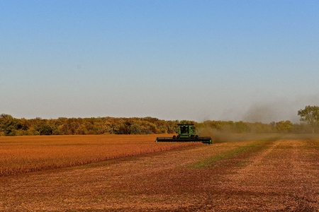 HALSTAD, MINNESOTA,  October 7 2017: The green self propelled combine in the autumn lighting of a soybean field is aproduct of John Deere Co, an American corporation that manufactures agricultural, construction, forestry machinery, diesel engines,, and dr