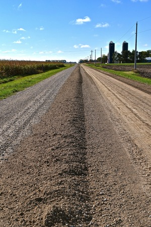 A road grader leave leaves a ridge of sand after the first pass over a gravel road