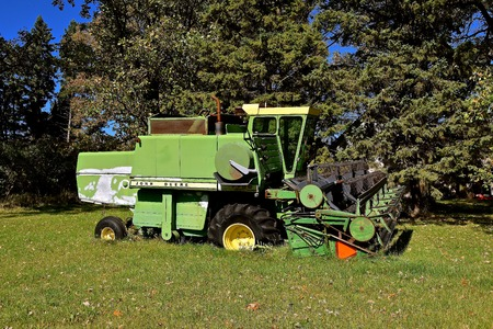 DETROIT LAKES, MINNESOTA, Sept 26, 2017: The faded self propelled John Deere combine left for salvage is a product of John Deere Co, an American corporation that manufactures agricultural, construction, forestry equipment, machinery, and diesel engines, Editorial