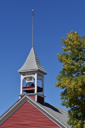 The bell and belfry belong to the red one room rural schoolhouse building.