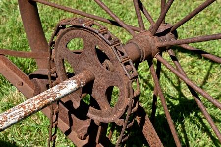 A chain driven cogwheel on an axle an old spoke steel wheel