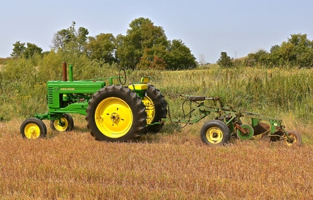 ROLLAG, MINNESOTA, Sept 2, 2017: A restored A John Deere tractor hooked to a three bottom trip plow is ready for demonstrations at the annual WCSTR farm show in Rollag held each Labor Day weekend where 1000s attend.