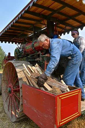 ROLLAG, MINNESOTA, Sept 2, 2017: An unidentified man pulls firewood out of the tender box to feed a steam engine   at the annual WCSTR farm show in Rollag held each Labor Day weekend where 1000s attend. Editorial