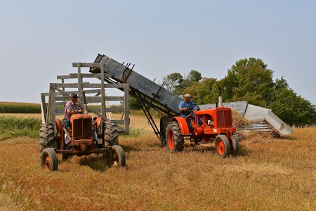 ROLLAG, MINNESOTA, Sept 2, 2017: Old Allis Chalmers tractors and an Acme Loader are harvesting grain in a field demonstration at the annual WCSTR farm show in Rollag held each Labor Day weekend where 1000s attend.