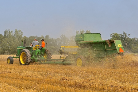ROLLAG, MINNESOTA, Sept 2, 2017:A field demonstration of a tractor pulling a power take-off John Deer Combine 42 at the annual WCSTR farm show in Rollag held each Labor Day weekend where 1000s attend.