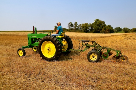 ROLLAG, MINNESOTA, Sept 2, 2017: An unidentified operator of an A john Deere tractor and two bottom plow are ready for field demonstrations at the annual WCSTR farm show in Rollag held each Labor Day weekend where 1000s attend.