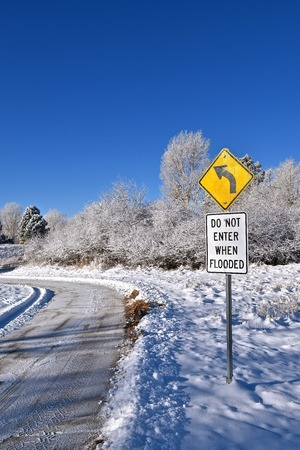 Road sign DO NOT ENTER WHEN FLOODED along a  plowed road  after a snowfall.