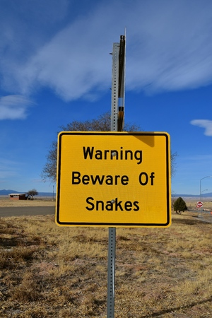 Warning sign to be aware of snakes in the area Stock Photo