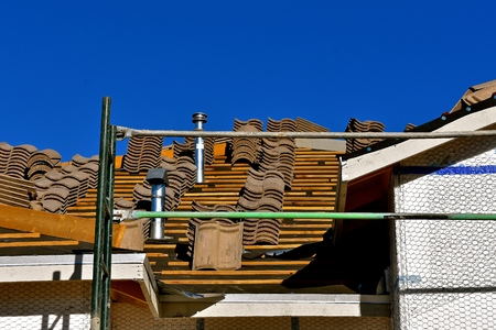 Tile shingles are stacked on the top of a roof under construction