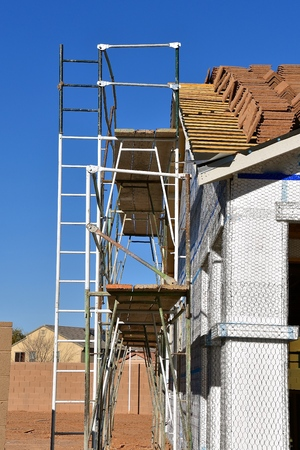 A building is under construction with tile  shingles on the roof and a scaffolding in place.