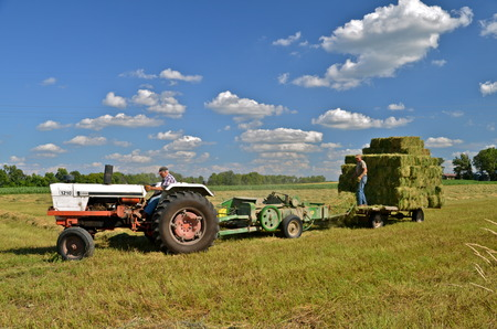 OSAKIS, MINNESOTA, July 31, 2013: The White tractor pulling the baler is a product of AGCO produced from 1991-2001 when White merged with AgCO-Allis.
