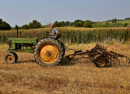 ROLLAG, MINNESOTA, Sept 2, 2017: An unidentified operator of an Old John Deere is heading for a field cultivator demonstration at the annual WCSTR farm show in Rollag held each Labor Day weekend where 1000`s attend.