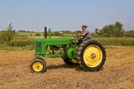 ROLLAG, MINNESOTA, Sept 2, 2017: An unidentified operator of an Old A John Deere is heading for a field demonstration at the annual WCSTR farm show in Rollag held each Labor Day weekend where 1000's attend. Editoriali
