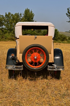 Parked in a harvested wheat field is restored old classic car, 免版税图像