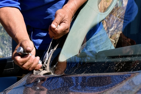 Removing stripping and metal clips in the process of replacing a pickup windshield.