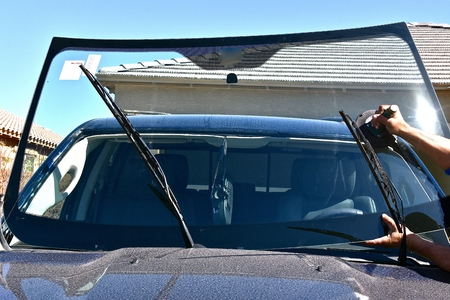 Replacing a new windshield on a pickup with the aid of a suction cup. Archivio Fotografico