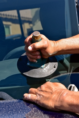 Installing a new windshield in a pickup with the aid of a suction cup.