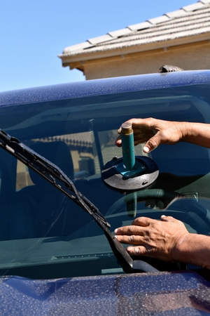 Replacing a new windshield on a pickup with the aid of a suction cup. Stockfoto