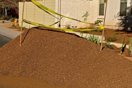 A load of crushed red rock is dumped on a street with caution tape expressing danger.