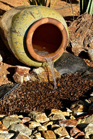 Water from a underground hose flows through a flower pot into a pile of decorative rocks in a flower bed of an arid climate.