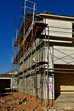 Side profile of a  building is under construction with scaffolding and tile shingles on the roof. Zdjęcie Seryjne