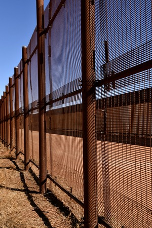 Two chain link fences with neutral territory in the middle provide barriers between Mexico and United States,