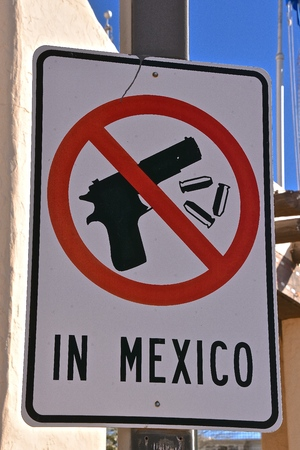 A sign on the Mexican, United States border provide a warning sign of no guns allowed in Mexico.