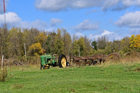 BEMIDJI, MINNESOTA,September 26, 2017. The worn out old John Deere tractor left in a field is a product of John Deere Co, an American corporation that manufactures agricultural, construction, forestry machinery, diesel engines, and drive trains.