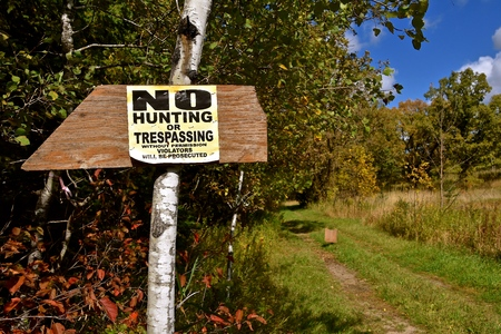 A NO HUNTING OR TRESPASSING sign tacked on a tree with a path leading into a wooded area Stock Photo
