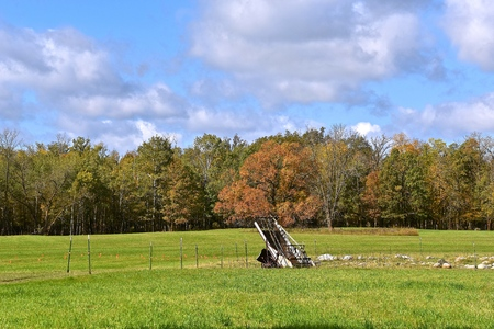 An old hay walker is left in a field with a background of trees in the early season of fall