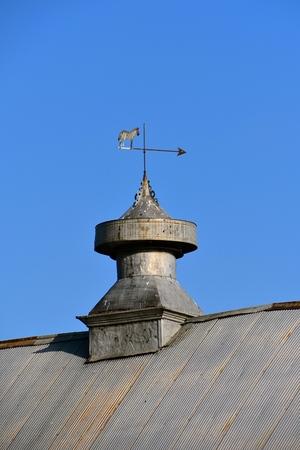 오래 된 금속 큐폴라는 금속 지붕 헛간의 지붕에 앉아