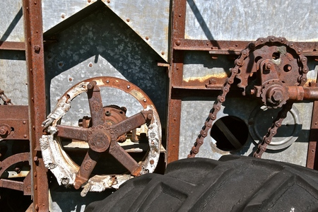 Rusty gears and chains on the side of an old threshing machine.