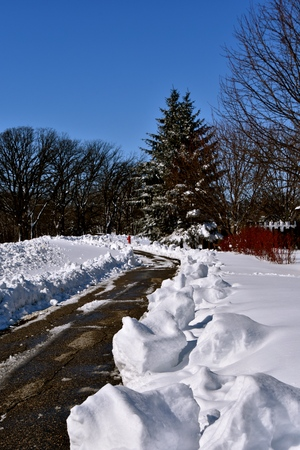 Huge piles of snow are left when a plow cleans a sidewalk after a spring snowstorm