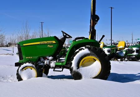 MOORHEAD, MINNESOTA, 5 marca 2018: Pokryty śniegiem ciągnik 3025E John Deere to produkt amerykańskiej korporacji John Deere Co, która produkuje maszyny rolnicze, budowlane, leśne i silniki Diesla. 8 kwietnia 2017: 3025E Joh
