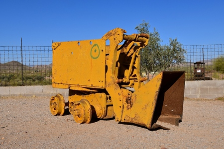 An old mining loader with a front end bucket designed to travel over railroad tracks