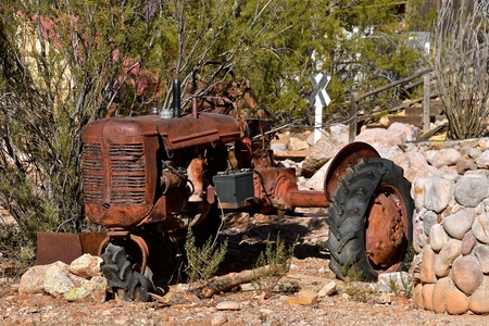Very old rusty remains of a tractor is left in a rock pile and brush.