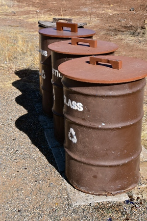 Four old metal barrels for the collection of glass, plastic, cans, and paper in a recycling effort Stock Photo