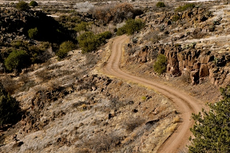 A winding dirt and gravel road leads through the side of a deep canyon in  rugged and a rocky and rugged landscape 版權商用圖片
