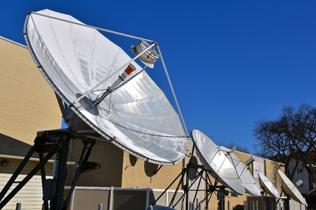 A row of outdoor television satellite dishes