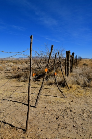 A barber wire gate stretches across a dusty desert trail
