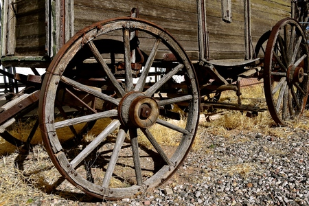 Hub, rim, and spokes of old wheels supporting a weathered wood wagon