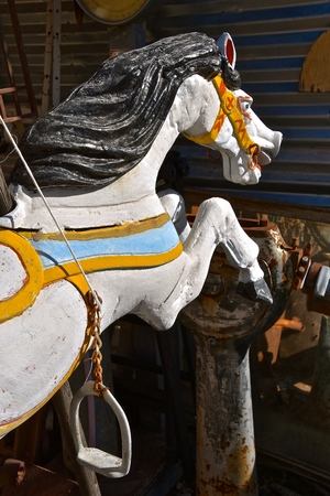 The head of a galloping painted horse with a bridle and stirrups either carved from wood or formed from plaster of paris.
