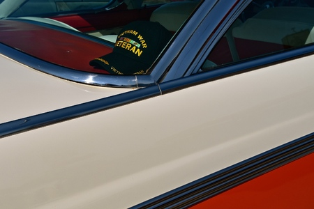 The cap of a Vietnam Veteran lies in the back window of a classic old car. Editorial
