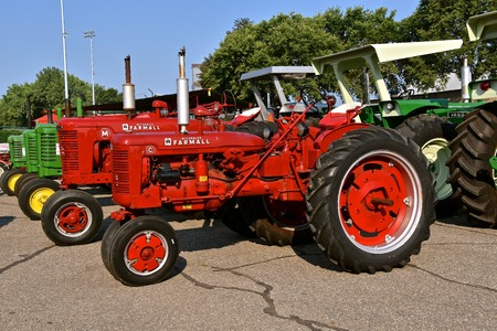 YANKTON, SOUTH DAKOTA, August 19, 2017: A restored vintage Farmall C and M tractors are displayed at the annual Riverboat Days celebrated the third weekend of August Banque d'images - 98810865