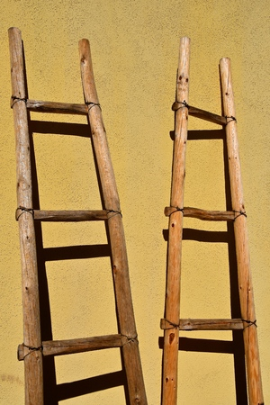Several unique homemade ladders lean against the yellow siding of a house