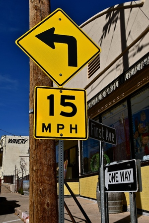 An old sign directing traffic to turn left and do not exceed 15 mile per hour Stock Photo - 98965148