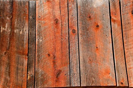 Old weathered fence boards with a red texture