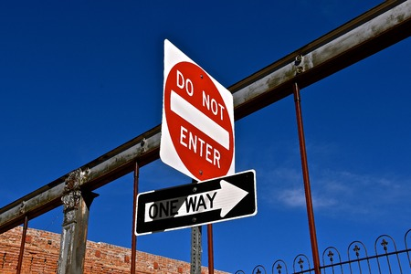Signs attached to a steel fence of a NO NO ENTRY zone on a ONE WAY street. Stock Photo