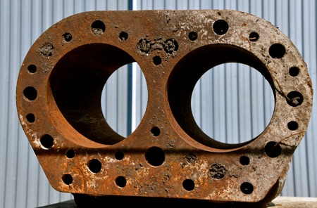 Rusty block of an old tractor engine exposing the space for the cylinders