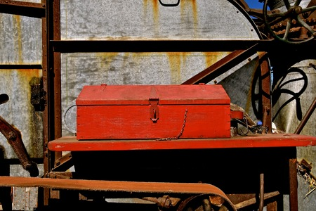 An old red wood handmade toolbox resides on a ledge of a vintage threshing machine. Stockfoto